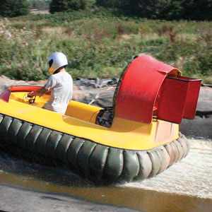 An example of the Hoverdays gift experiences where a photo has been taken of a man driving a hovercraft over water with a helmet on, in the countryside.